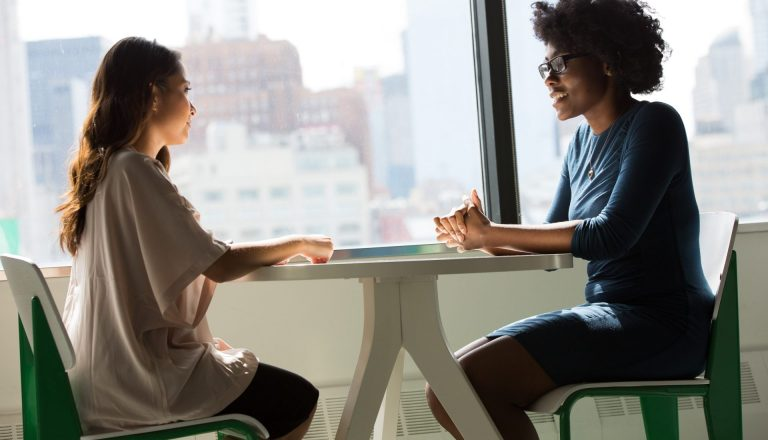 Two women sitting at a table for a career interview